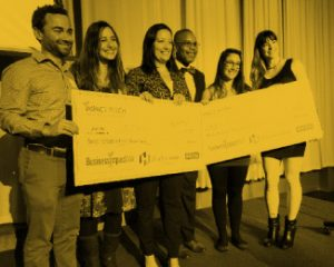 Entrepreneurs holding check for their winning business at Impact Pitch